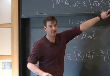 man teaching in front of black board